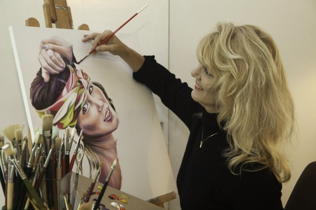artist in her fifties painting a portrait photo