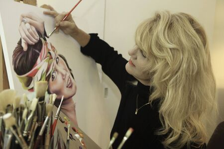 painting: artist in her fifties painting a portrait