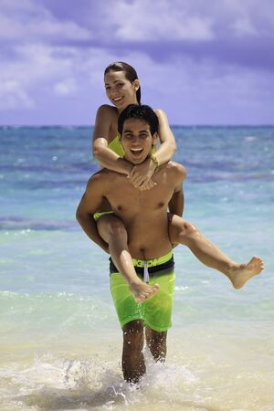 carrying: couple in the ocean riding piggyback