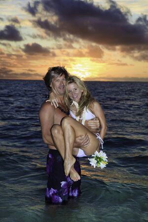 newlywed couple in their forties in the ocean in hawaii at sunrise 版權商用圖片