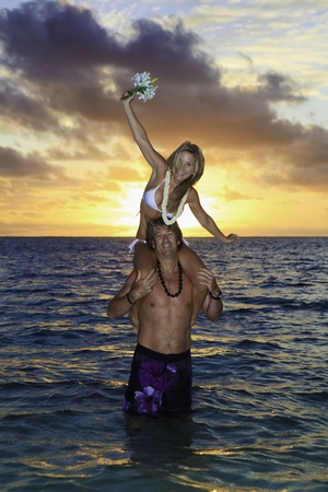 newlywed couple in their forties in the ocean in hawaii at sunrise photo