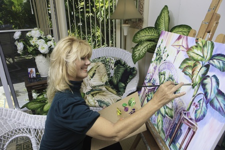 painting: beautiful blond artist in her fifties painting  Stock Photo