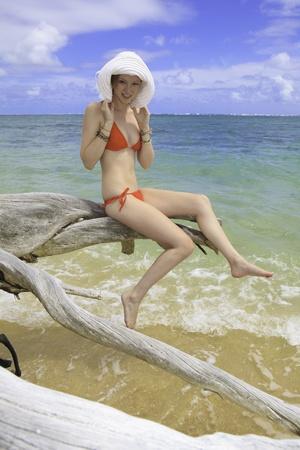 meisje in de rode bikini en hoed zit op een dode boom