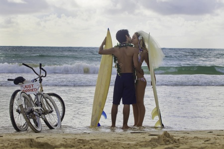 interracial marriage: newlywed couple at the beach with surfboard Stock Photo