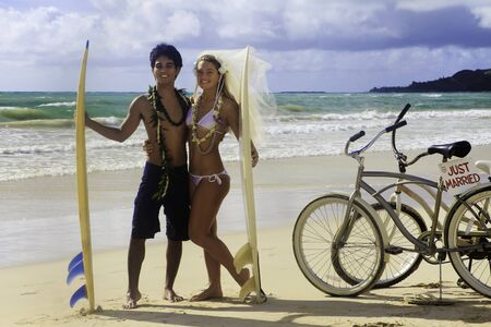 newlywed couple at the beach with surfboard photo