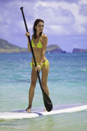young woman on a standup paddle board photo