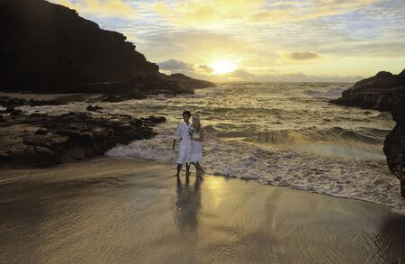 interracial marriage: newlywed couple at sunrise on Eternity Beach Stock Photo