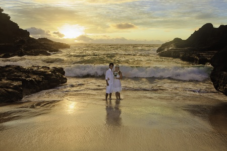 mixed flower bouquet: newlywed couple at sunrise on Eternity Beach Stock Photo