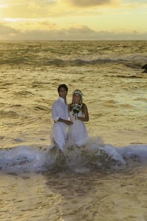 splash mixed: newlywed couple at sunrise on Eternity Beach Stock Photo