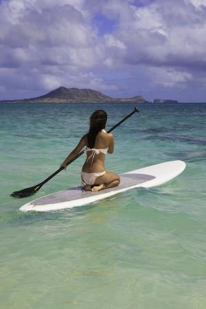 polynesian girl on a standup paddle board photo