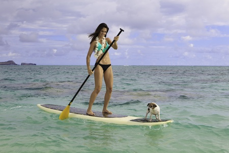 woman on her paddle board with her dog