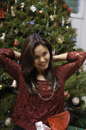 beautiful young woman at christmas with tree photo