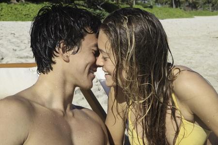 couple mixte: jeune couple s'embrassant sur la plage � Hawaii Banque d'images