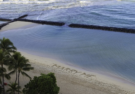 proposal of marriage:  marry me  written on the sand of waikiki