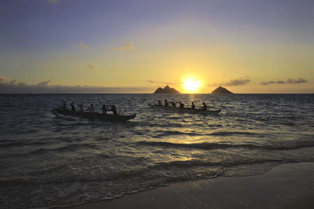outrigger: outrigger canoes paddle out from shore  Stock Photo