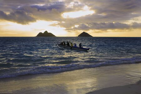 outrigger: an outrigger canoe heads out to sea at sunrise