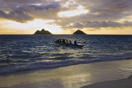 een outrigger kano staat aan het hoofd de zee bij zonsopgang