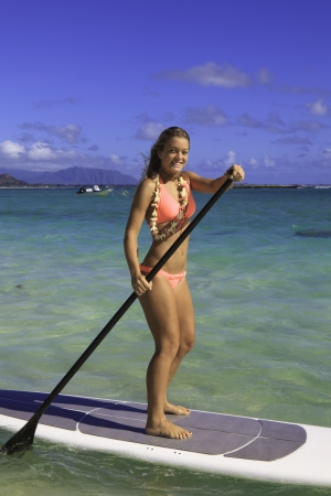 paddling: beautiful girl in bikini on her stand up paddle board