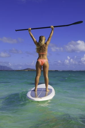 beautiful girl in bikini on her stand up paddle board photo