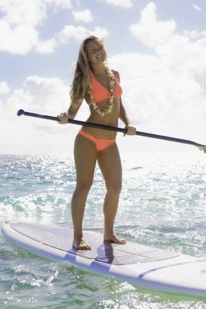 beautiful girl in bikini on her stand up paddle board