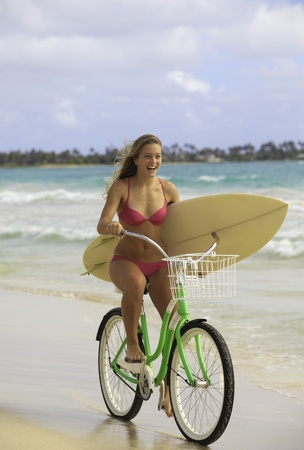 girl in pink bikini on bike at the beach with surfboard photo