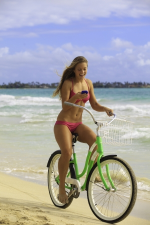 girl in bikini texting on cell phone at beach with bike Stock Photo