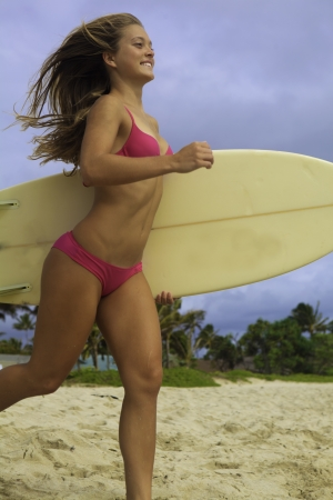 girl in pink bikini with surfboard running to the ocean photo