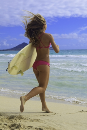 girl in pink bikini with surfboard running to the ocean Imagens