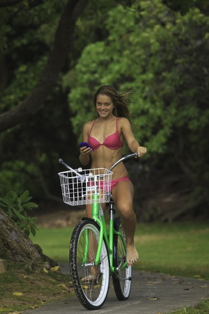 girl riding her bike in a park texting on her cell phone
