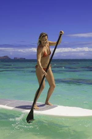 paddleboard: beautiful blond girl in bikini on her paddleboard