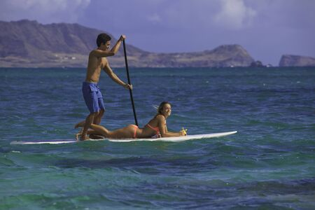 couple on standup paddle board in hawaii photo