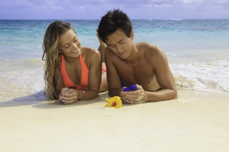young couple on the beach with their cell phone photo