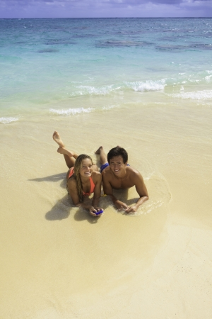 couple on the beach in hawaii with their cell phone photo