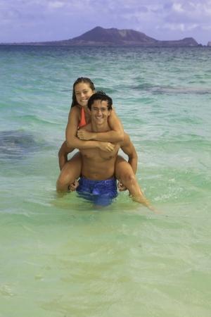 paar rijden piggyback in de oceaan Stockfoto