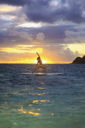woman doing yoga on her paddle board at sunrise