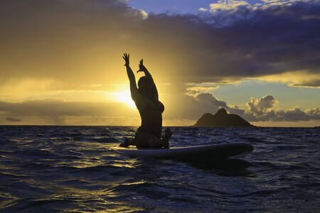 woman doing yoga on her paddle board at sunrise photo