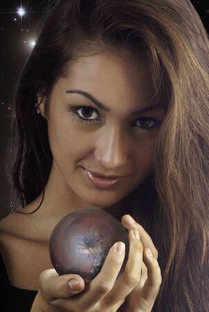 psiquico: mujer joven con una bola de cristal con una escena tropical en el interior