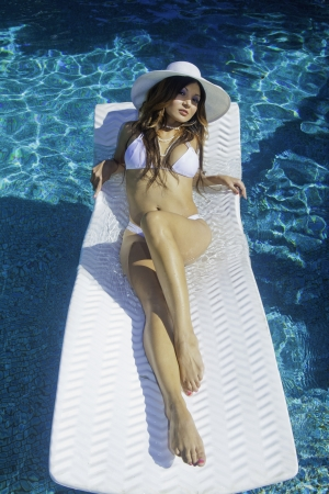 beautiful brunette in bikini floating on a pool raft Stock Photo - 16603495