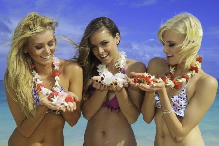 three girls in bikinis at a hawaii beach with flower lei Stock Photo