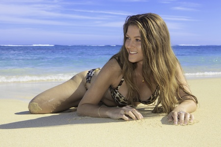 girl in bikini lying on a sandy beach in hawaii photo