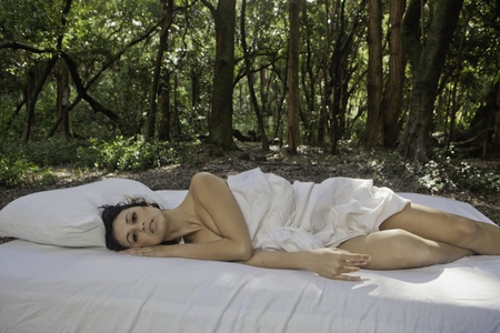 brunette naked: beautiful woman in bed in a forest Stock Photo