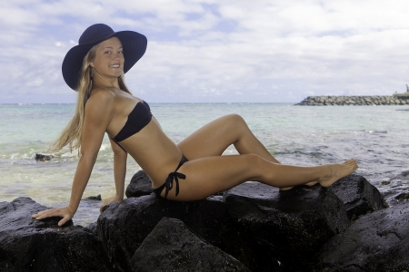 girl in bikini and hat lounging on lava rocks by the ocean photo