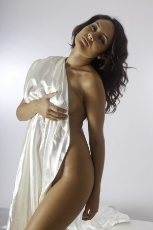 beautiful woman on white satin sheets