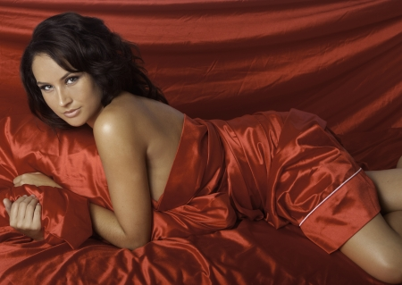 bed sheet: beautiful woman on red satin sheets Stock Photo