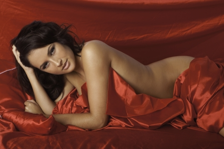 boudoir: beautiful woman on red satin sheets Stock Photo