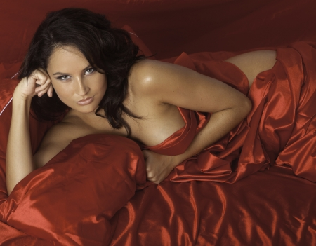 beautiful woman on red satin sheets Stock Photo