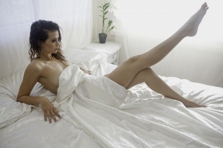 boudoir: beautiful girl on a bed of white satin
