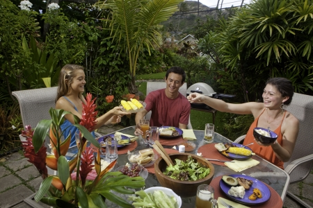 friends drinking: friends enjoying a barbecue lunch in a tropical garden
