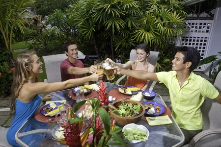 friends enjoying a barbecue lunch in a tropical garden photo