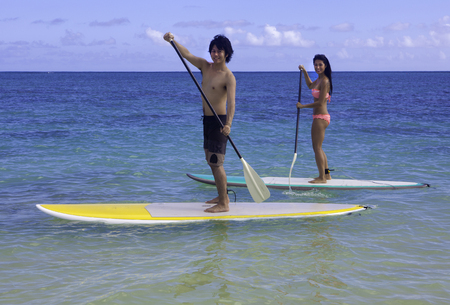 paddling: japanese couple on stand up paddleboards in hawaii